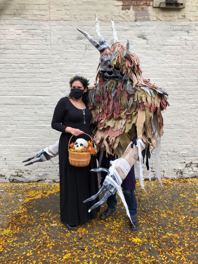 pagan woman in black with skull in a basket poses with a tall, wild man creature at Halloween 2020 in Brooklyn, NY.
